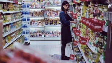 Junge Frau räumt in Supermarkt Regale ein.